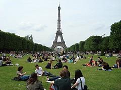 Ngồi thư giãn trên bãi cỏ gần tháp Eiffel ở Paris